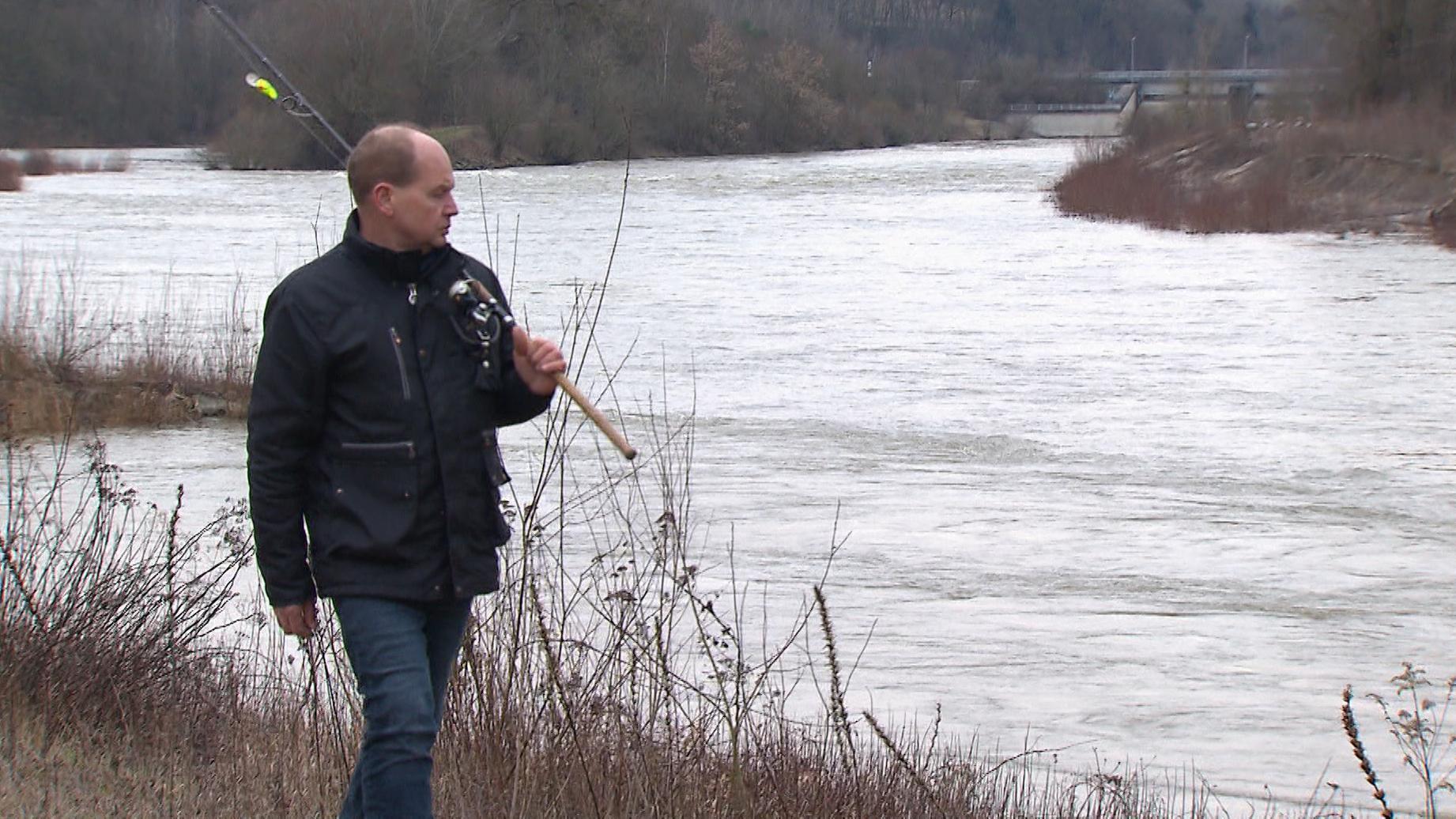 Ein Fischer geht mit seiner Angel an der Isar entlang