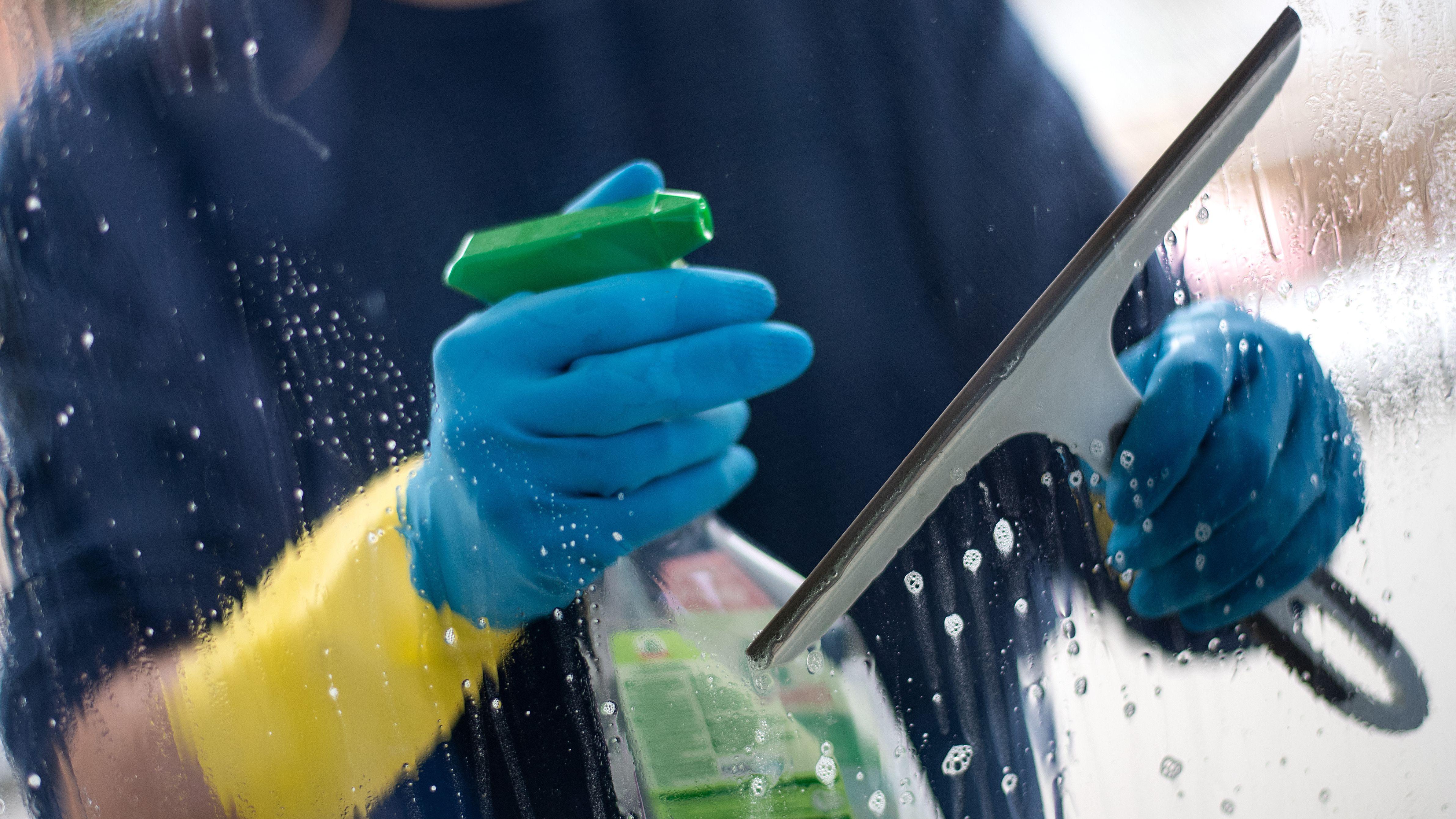 Ein Mann putzt in Gummihandschuhen Fenster