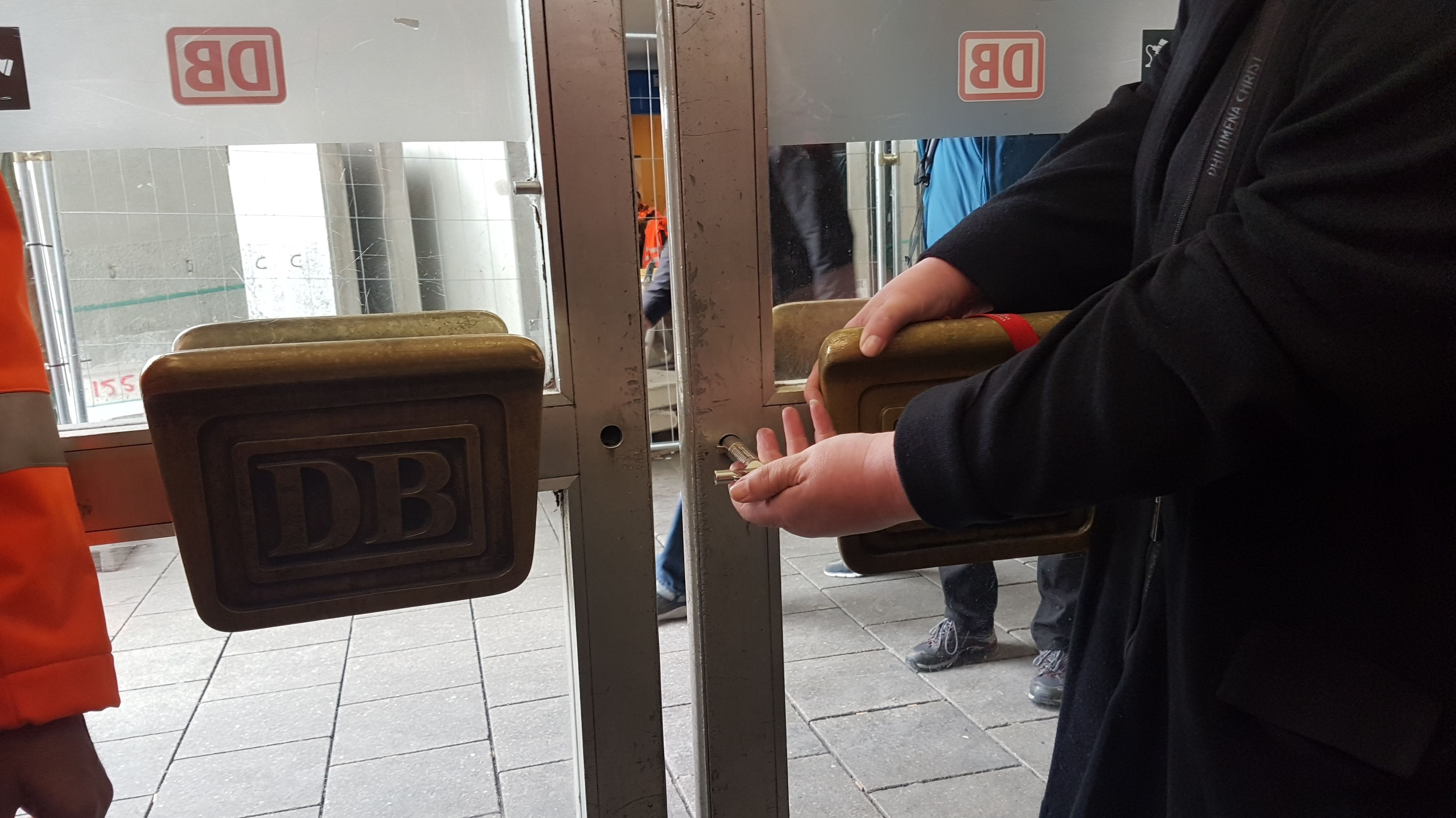 Die Bahnhofsmanagerin schließt symbolisch das Haupttor zur Schalterhalle ab.