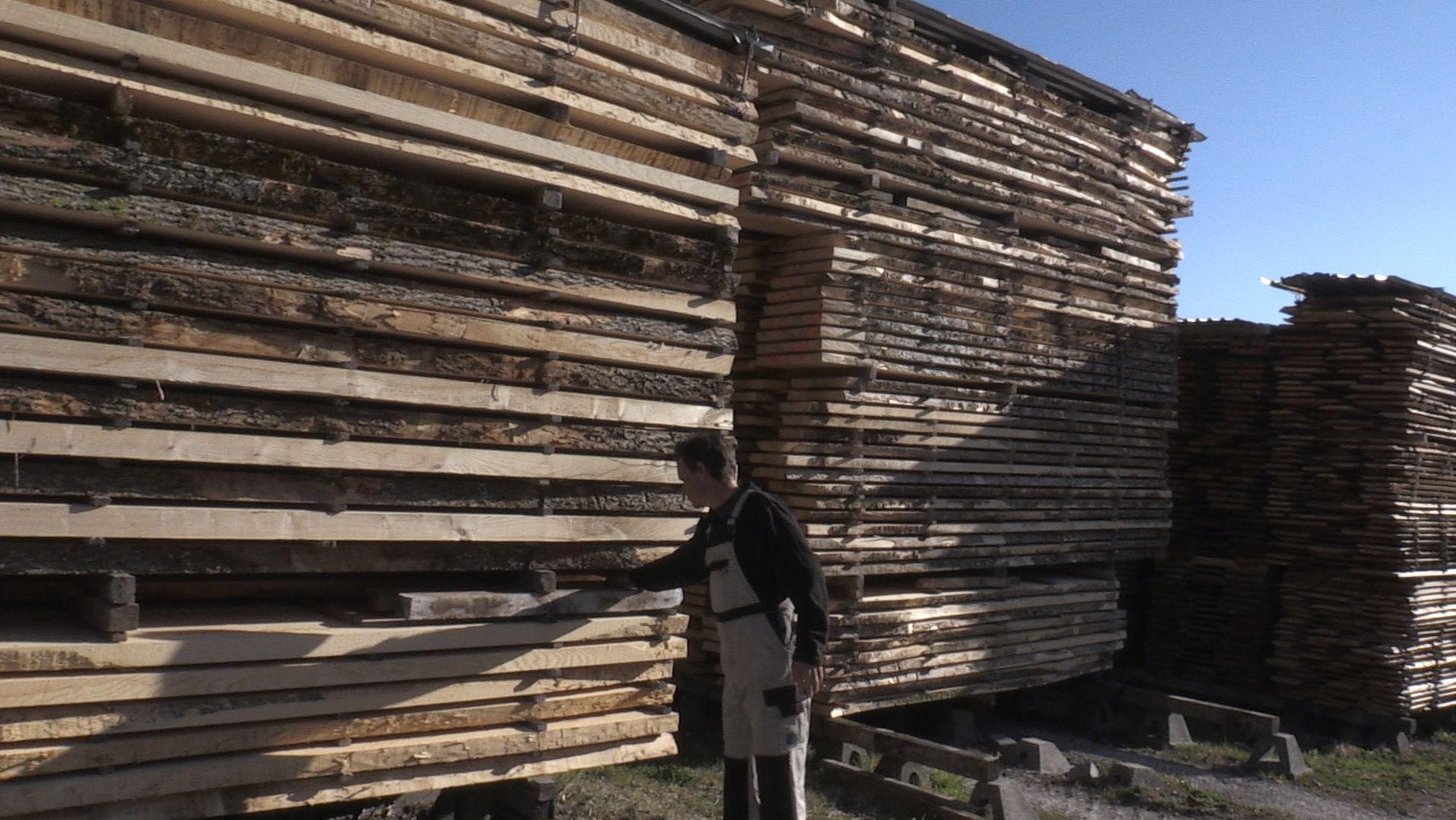 Ein Mitarbeiter eines Sägewerks vor mehreren riesigen Stapeln mit vorgeschnittenen Holzbrettern