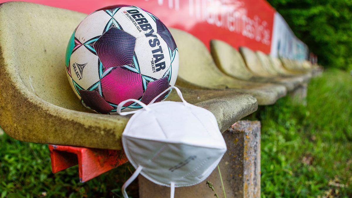 Ein Ball leigt auf einem Zuschauerstuhl bei einem Fußballspiel, dazu eine Maske.