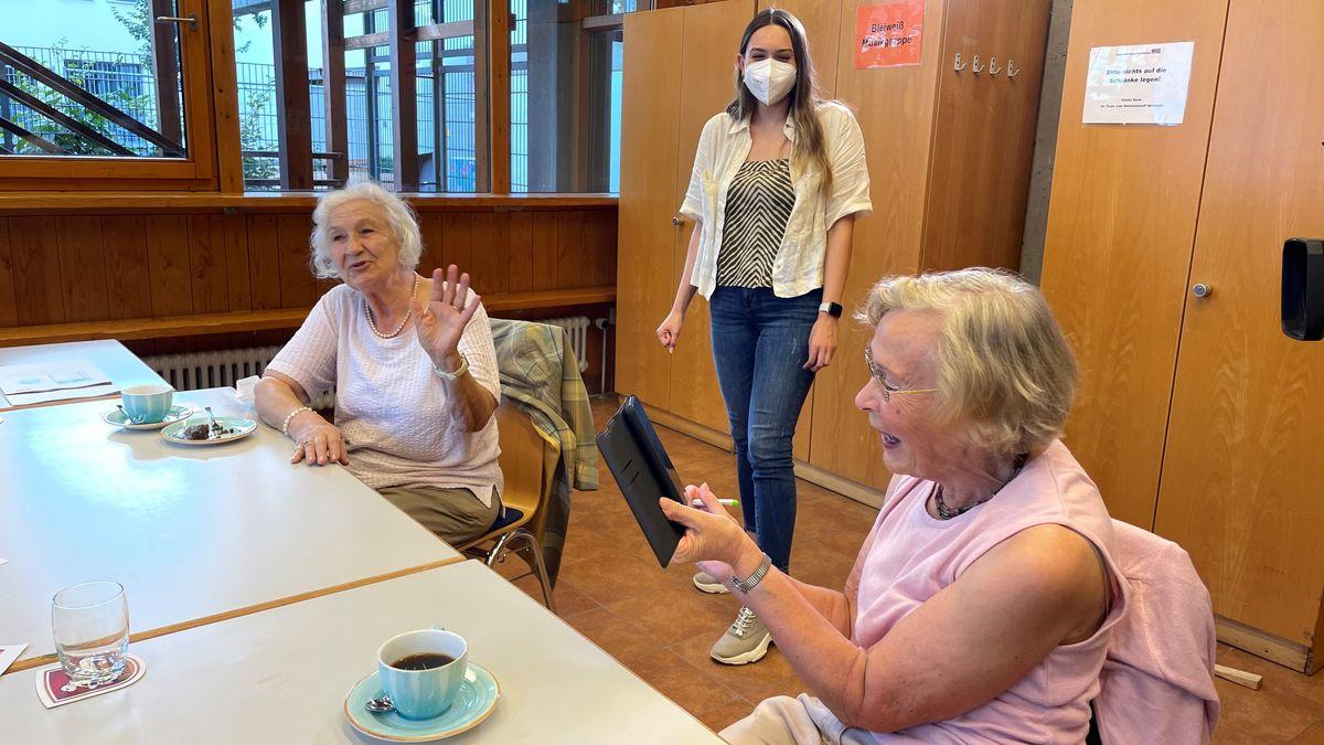 Zwei Seniorinnen sitzen bei Kaffee und Kuchen am Tisch, eine bedient ein Smartphone, die andere winkt ab. Im Hintergrund eine junge Frau mit Mund-Nasen-Schutz.