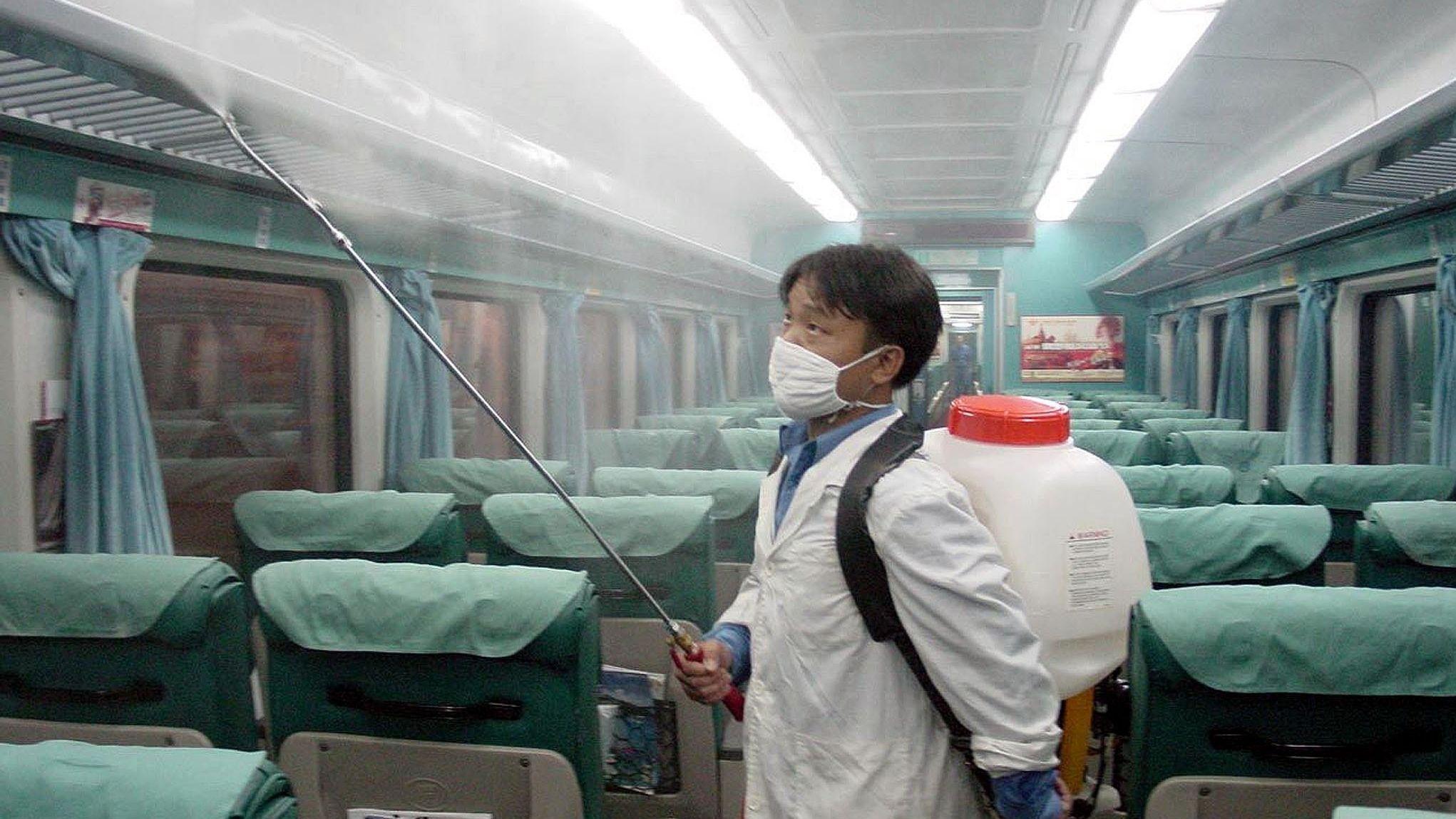 Ein medizinischer Mitarbeiter mit Schutzmaske sprüht Desinfektionsmittel in einem Zug in Shenzhen in Südostchina.