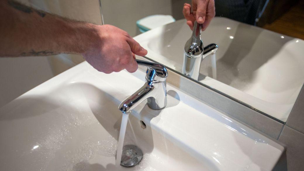Ein Mann öffnet einen Wasserhahn und lässt frisches Wasser fließen.