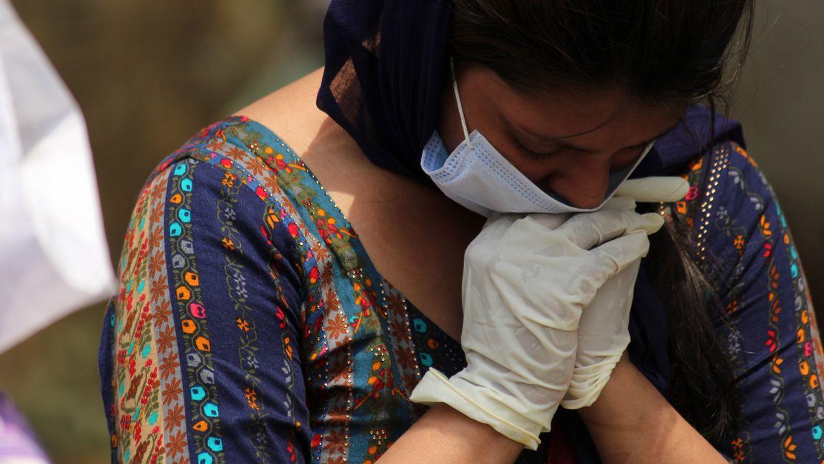 Indische Frau trauert auf einem Friedhof von Neu Delhi am Sarg eines verstorbenen Angehörigen (30.4.2021)