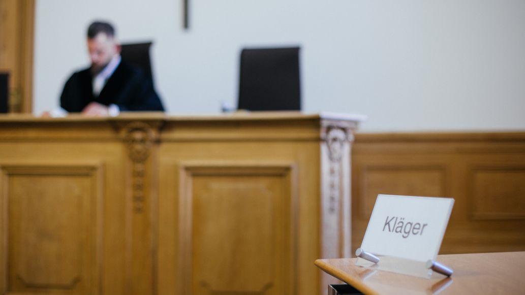 """Gerichtssaal. Ein Richter sitzt auf einem Stuhl. Auf einem Tisch davor steht ein Schild """"Kläger""""."""