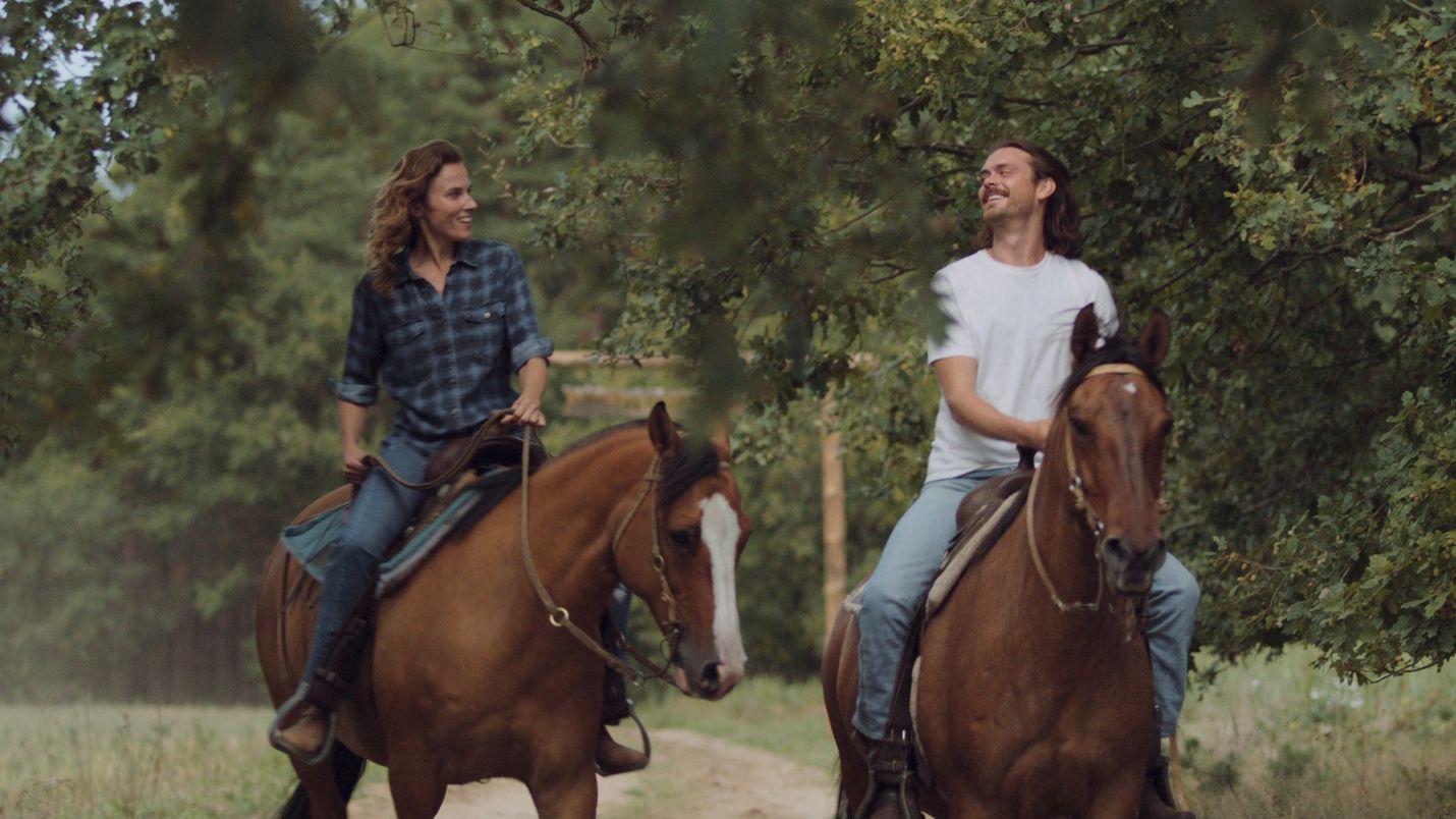 Die Filmgeschwister Lilly und Franz reiten auf Pferden auf einem Feldweg entlang.