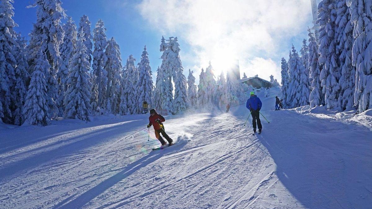 Skifahrer auf einem schneebedeckten Hang bei blauem Himmel.