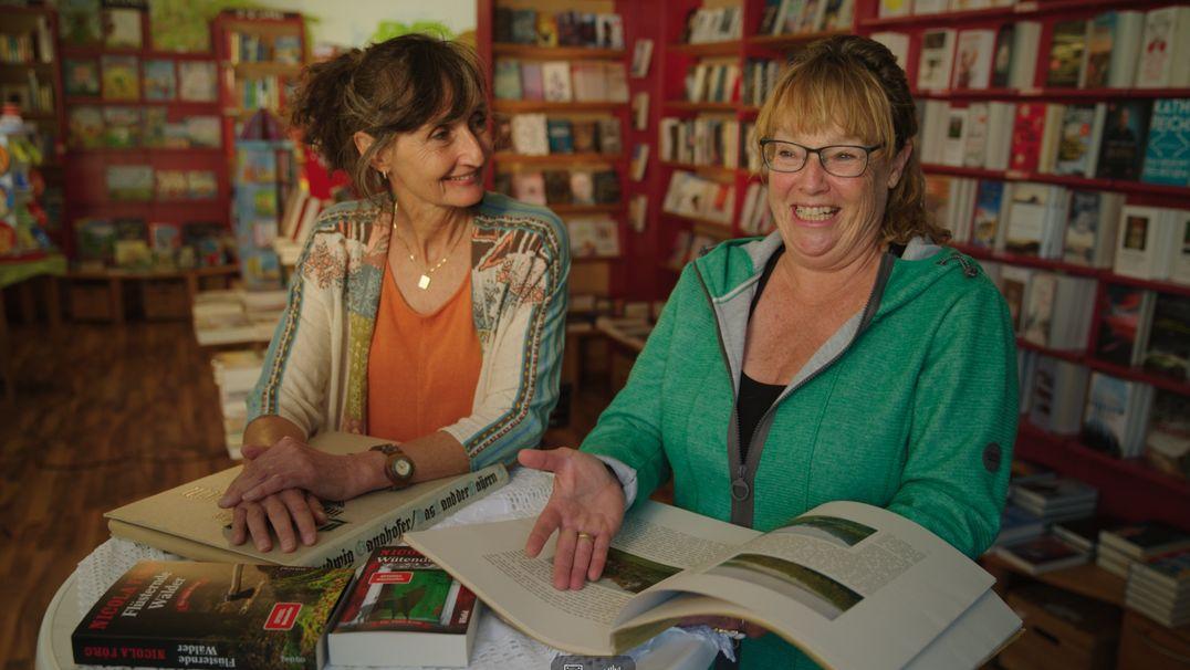 Zwei Frauen sitzen lachend in einem Buchladen.