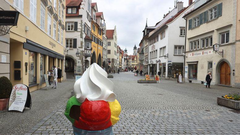 Ein Aufsteller für Eis steht in der Lindauer Fußgängerzone, in der nur wenige Menschen unterwegs sind.   Bild:picture alliance/dpa   Karl-Josef Hildenbrand