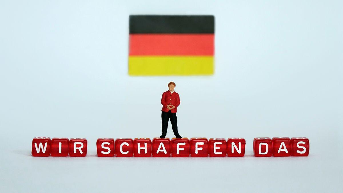 """ILLUSTRATION - Eine kleine Figur, die Bundeskanzlerin Angela Merkel darstellen soll, steht unter einer Deutschland-Fahne auf Buchstaben-Würfeln mit dem Schriftzug """"WIR SCHAFFEN DAS"""", aufgenommen am 18.03.2017."""