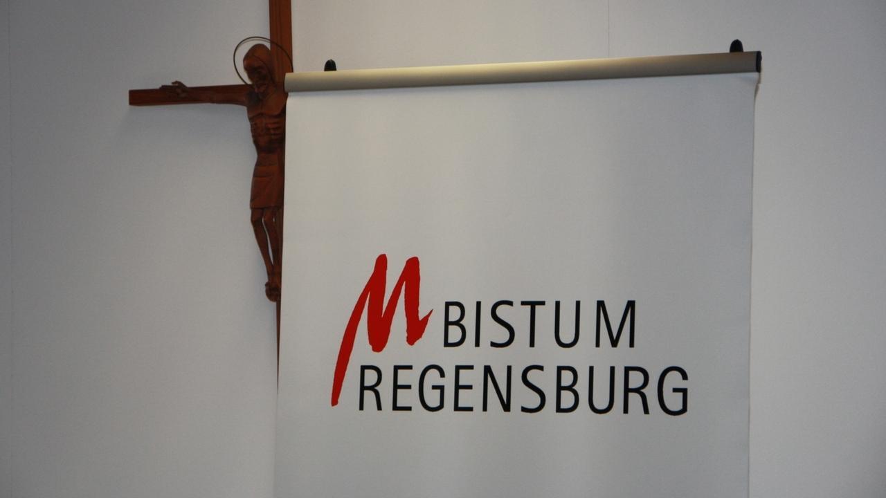 """Ein Plakat mit der Aufschrift """"Bistum Regensburg"""" vor einem Kruzifix (Symbolbild)"""