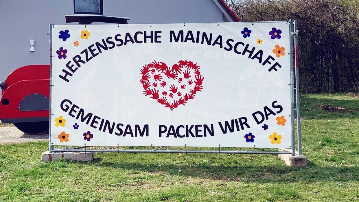 """Plakat mit Aufschrift """"Herzenssache Mainaschaff - gemeinsam packen wir das"""""""