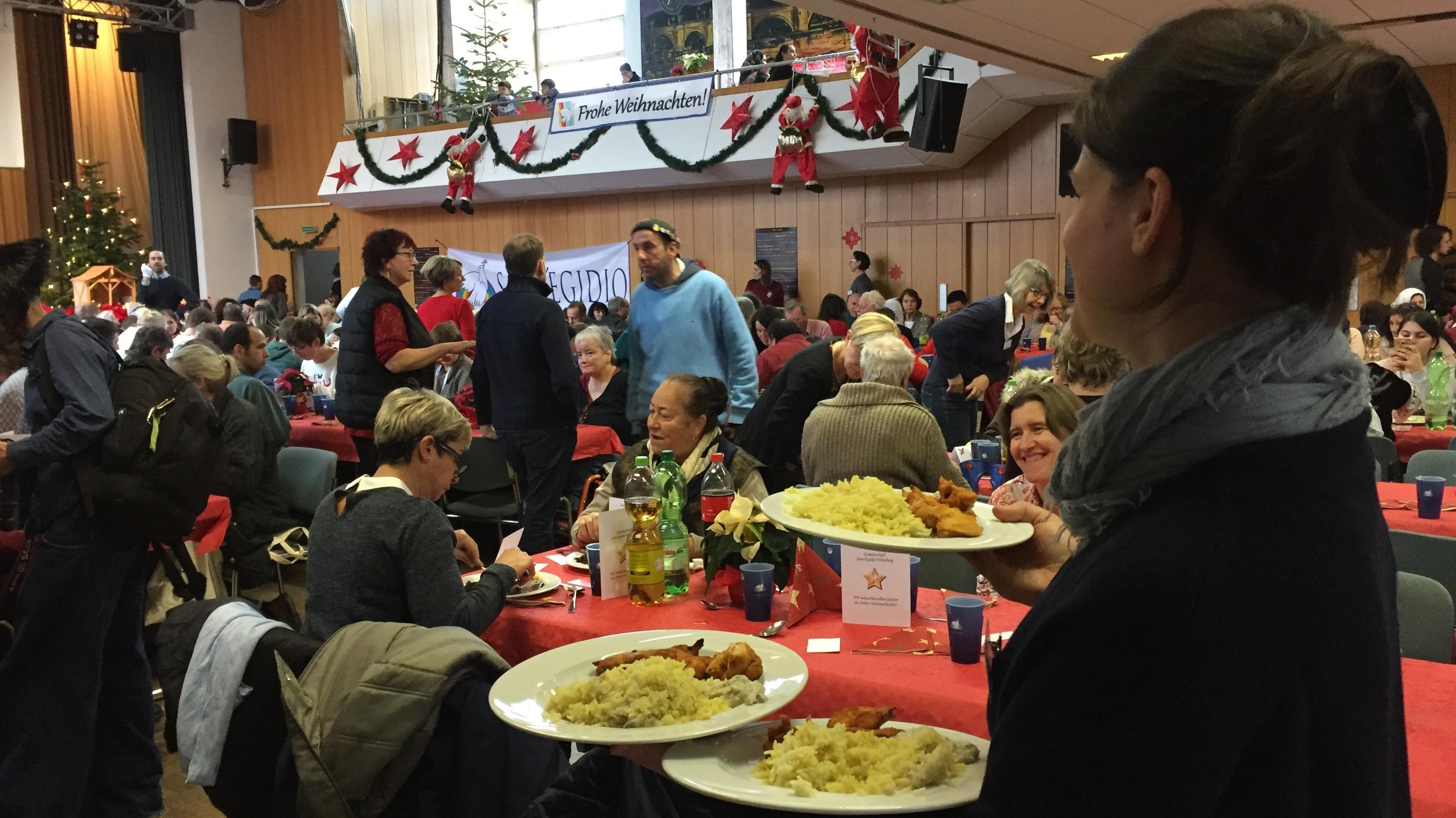 Eine von 400 freiwillige Helfern trägt Essen auf. Im großen Festsaal des Gemeindezentrum Heilig Kreuz in Würzburg gab es für Hähnchenbrust mit Reis für die geladenen Gäste: Alte, Alleinstehende, Bedürftige, Flüchtlinge oder Obdachlose.