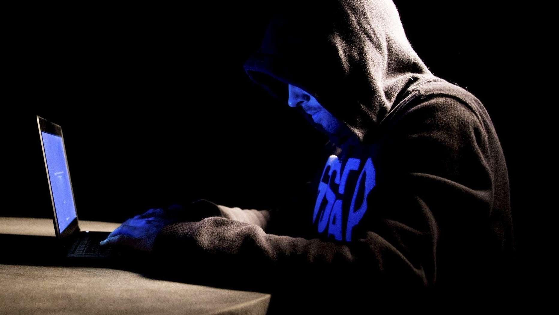 Mann mit Kapuze an einem Computer