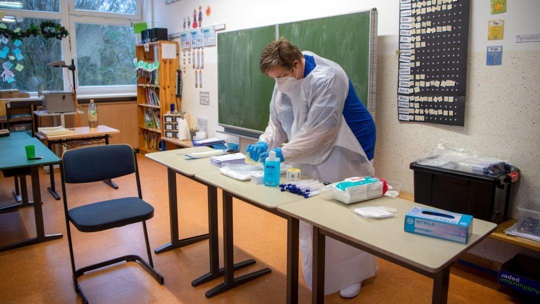 Ein mobiles Test-Team bereitet sich im Klassenraum einer Grundschule auf die Probenentnahme für PCR-Tests vor.