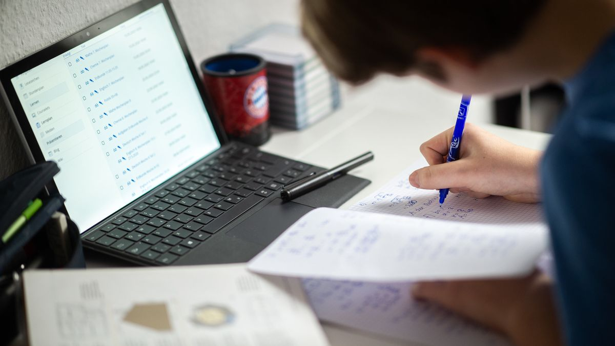 Ein Schüler sitzt in seinem Zimmer am Schreibtisch und erledigt Aufgaben im Rahmen des Homeschoolings