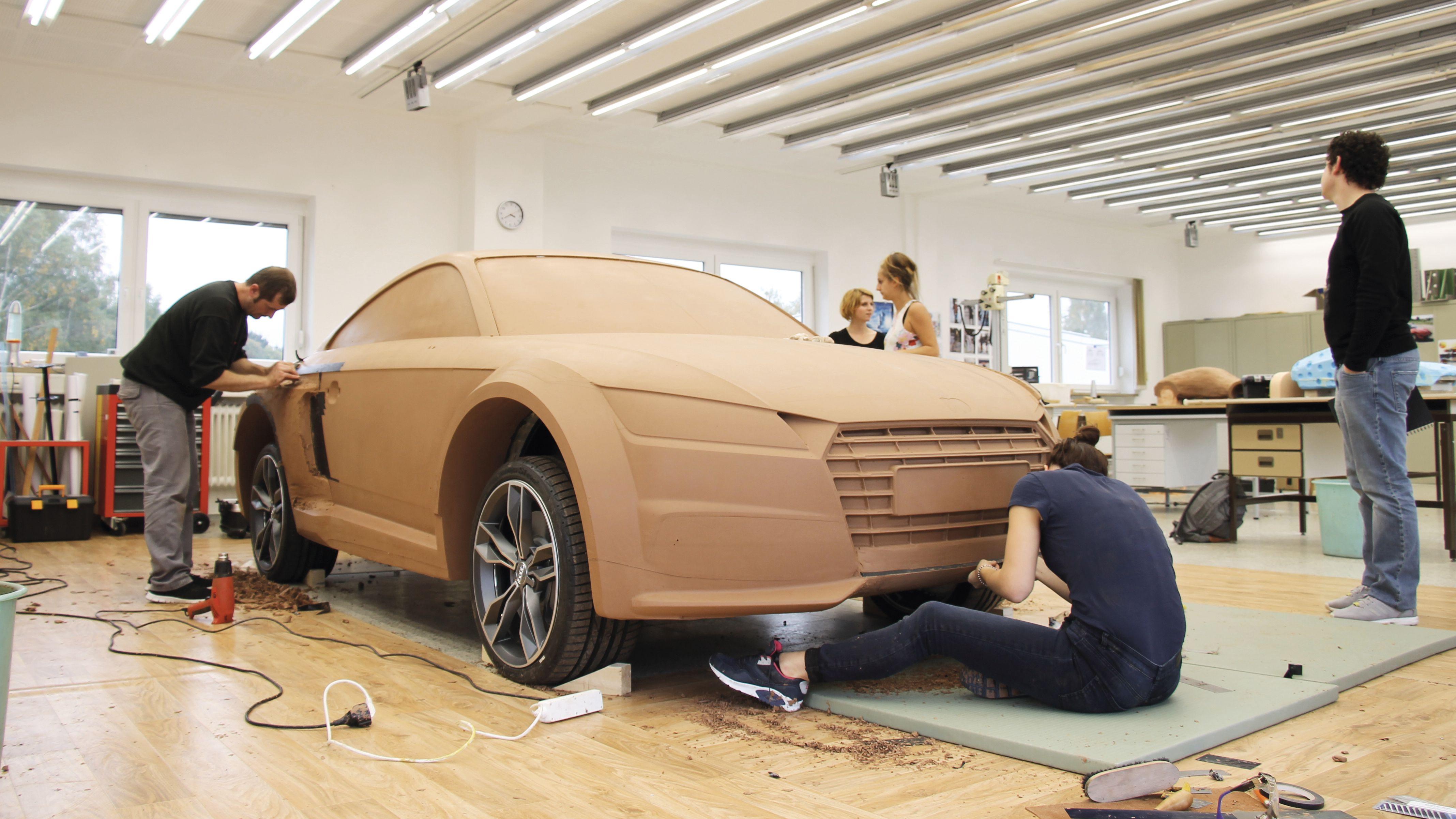 Studierende arbeiten an der Karosserie eines Autos