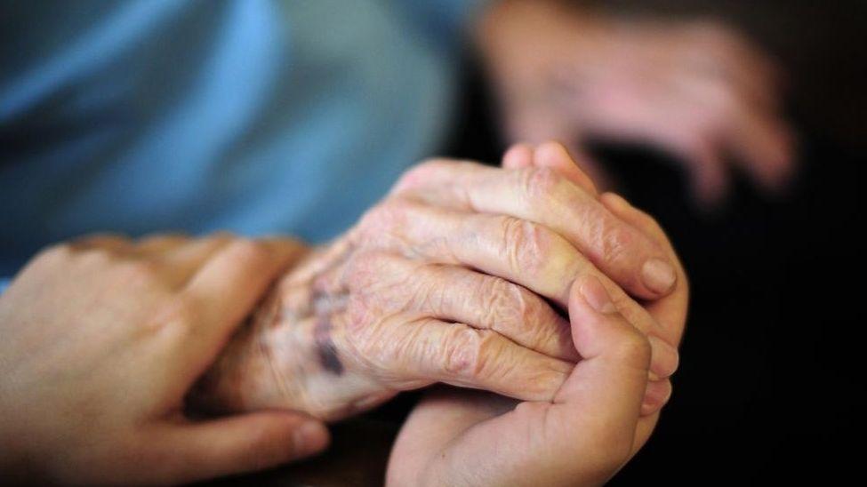 Symbolbild: Eine jüngere Frau hält die Hand einer Älteren.