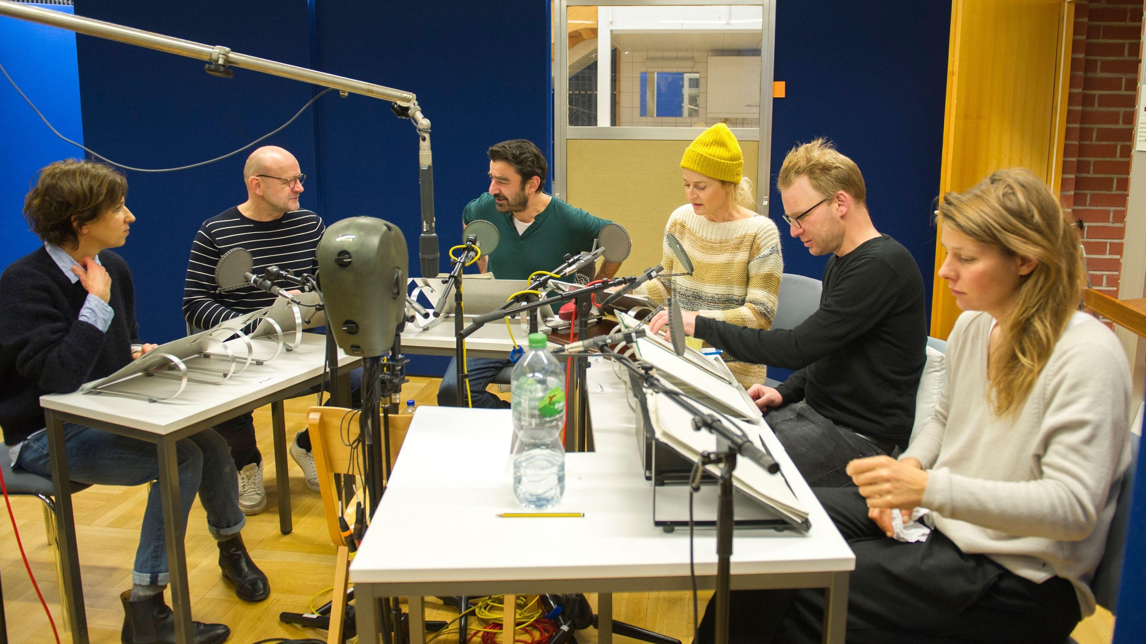 """Hörspiel-Produktion """"Die Schicksalsmaschine"""": sechs Schauspieler sitzen um einen Tisch"""