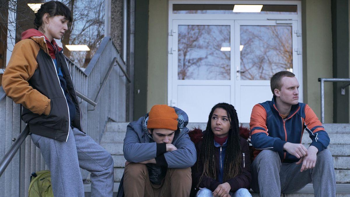 """Szene aus """"Nackte Tiere"""": Drei Jugendliche sitzen auf einer Treppe, einer steht"""