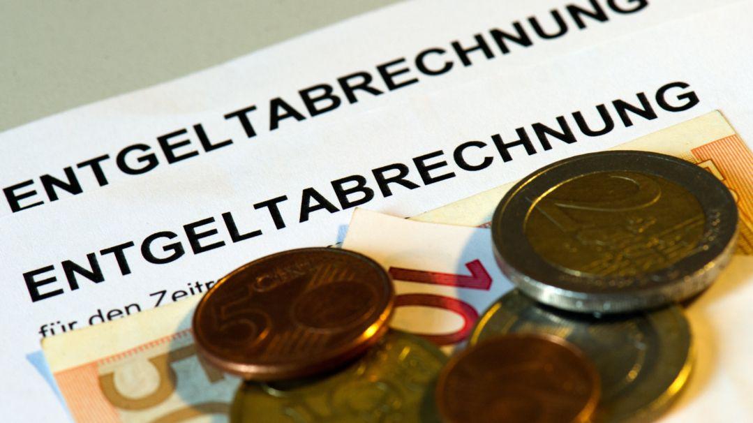 Euromünzen und Euroscheine liegen auf Entgeltabrechnungen.