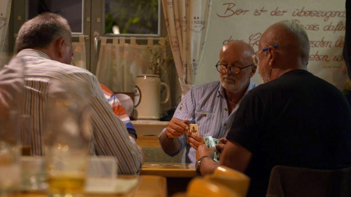 Vier Männer sitzen in einer Kneipe am Tisch und spielen Karten.