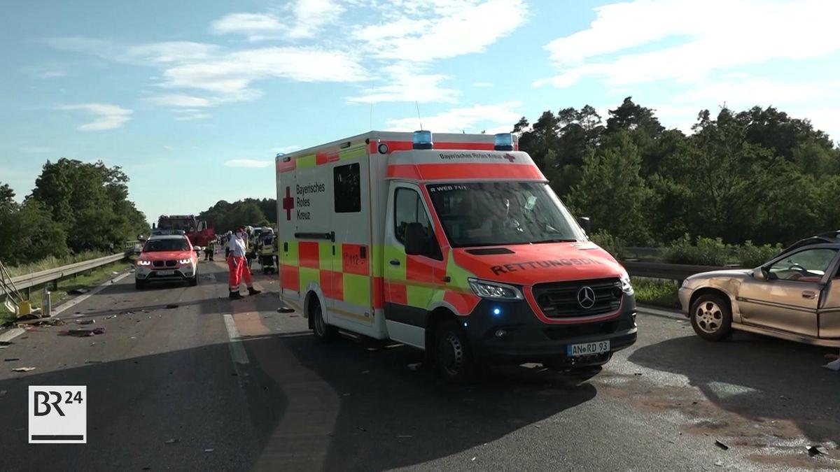 Krankenwagen neben Unfallfahrzeug auf der Autobahn.