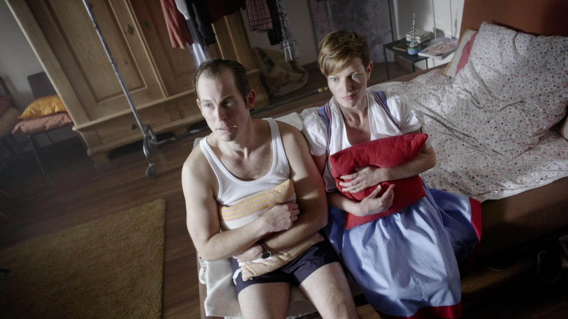 """Filmszene aus """"Akte Lansing"""": Ein Mann und eine Frau sitzen, Kissen an den Leib gedrückt, auf der Bettkante"""