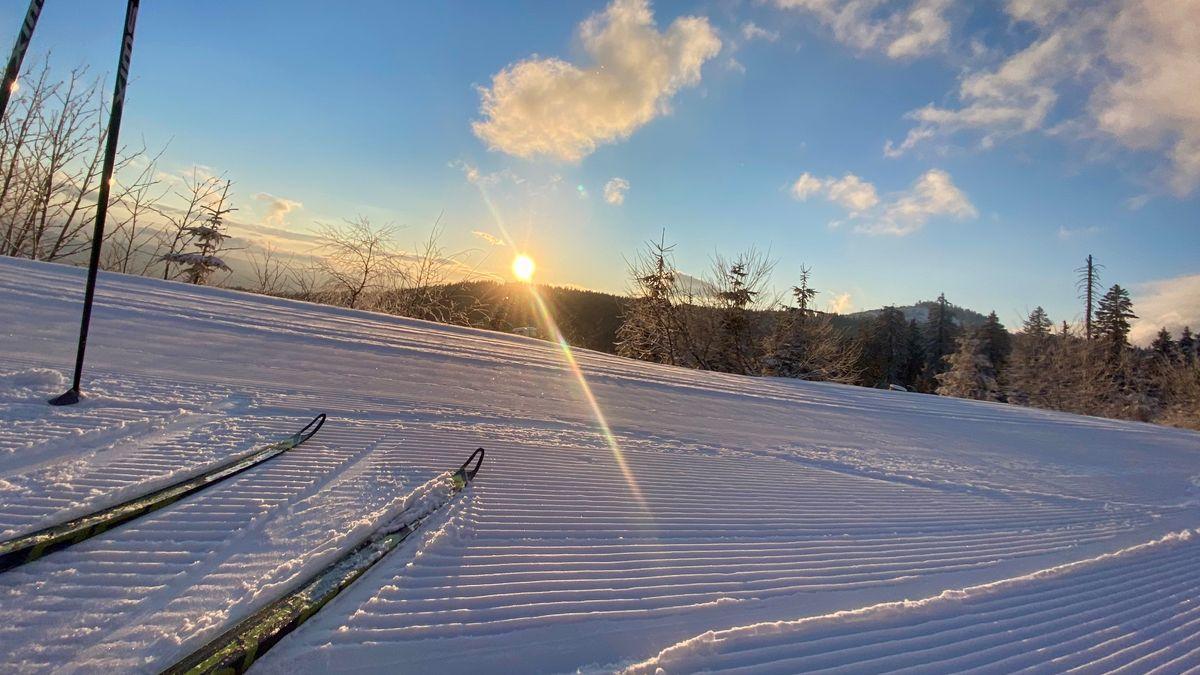 Tourenski auf einer Skipiste beim Sonnenuntergang