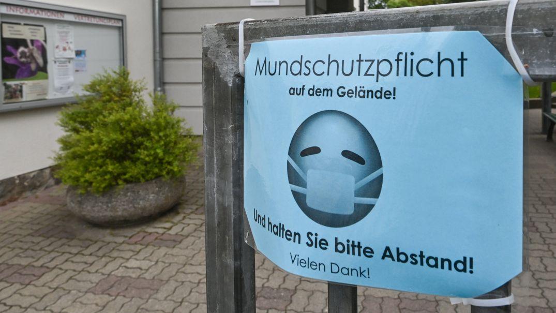Frankfurt (Oder): Ein Schild mit der Aufschrift «Mundschutzpflicht auf dem Gelände! Und halten Sie bitte Abstand! Vielen Dank!» am Tor zu einer Grundschule.