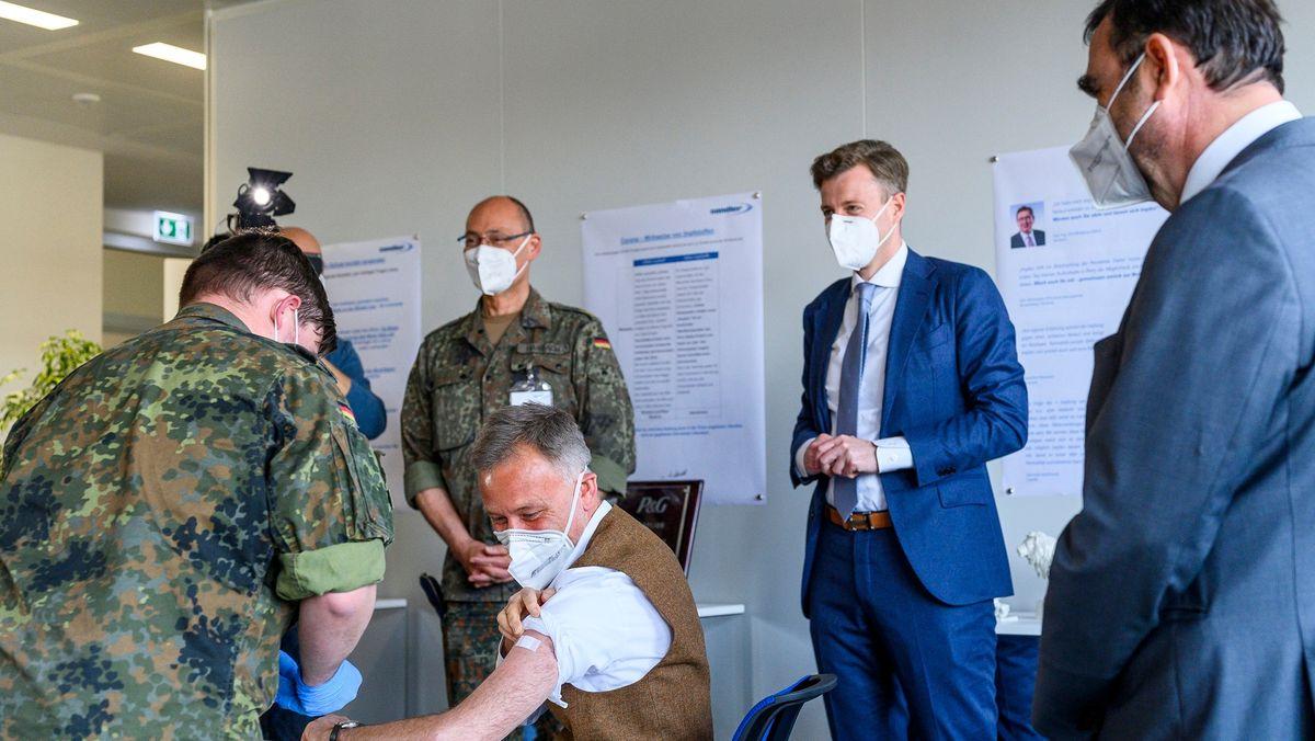 Bayerns Gesundheitsminister Klaus Holetschek (rechts) sieht einem Mitarbeiter der Sandler AG bei dessen Impfung zu.