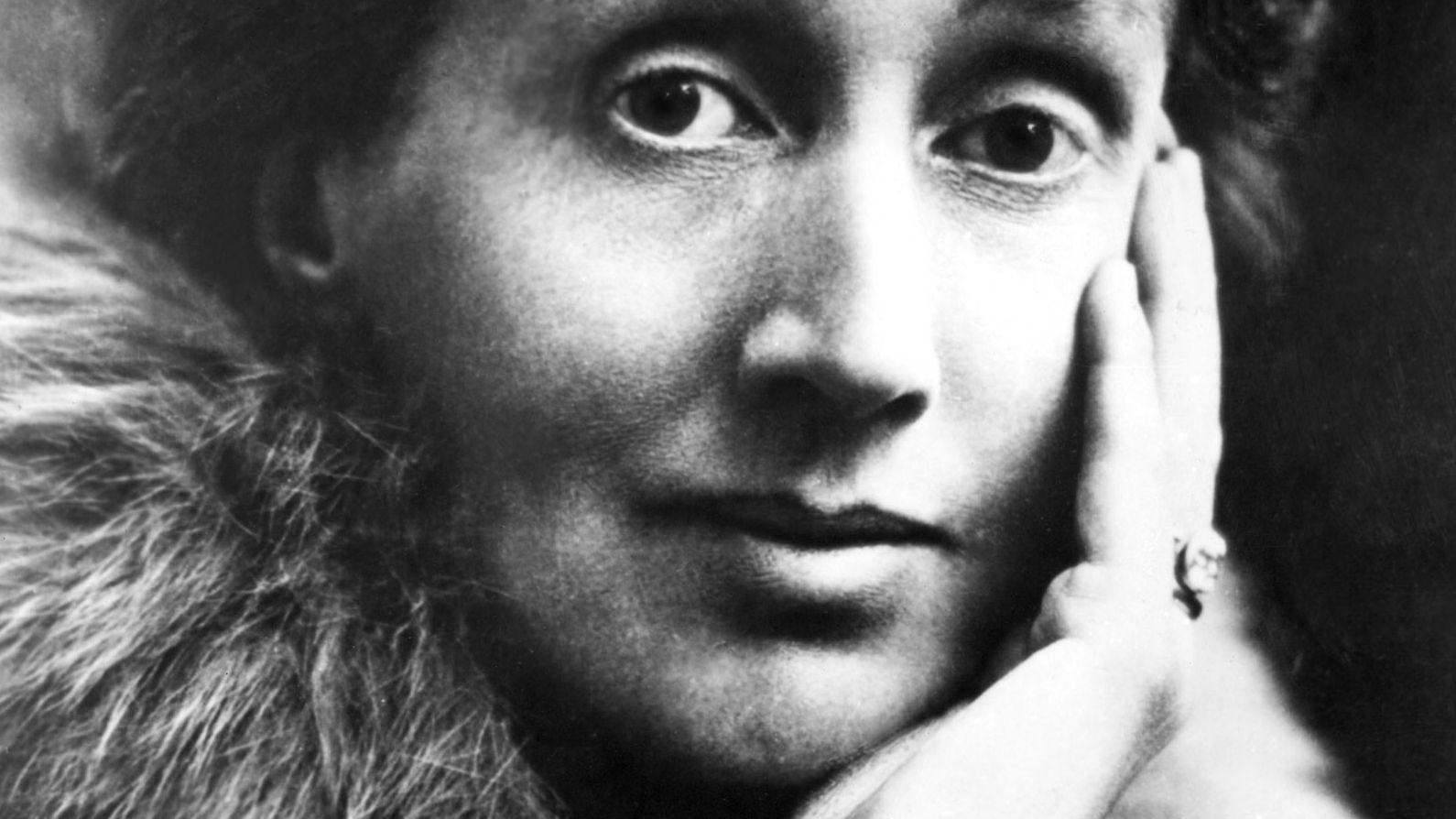 Virginia Woolf blickt, das Gesicht in eine Hand gestützt, mit weit geöffneten Augen in die Kamera (undatiertes Schwarzweißfoto)