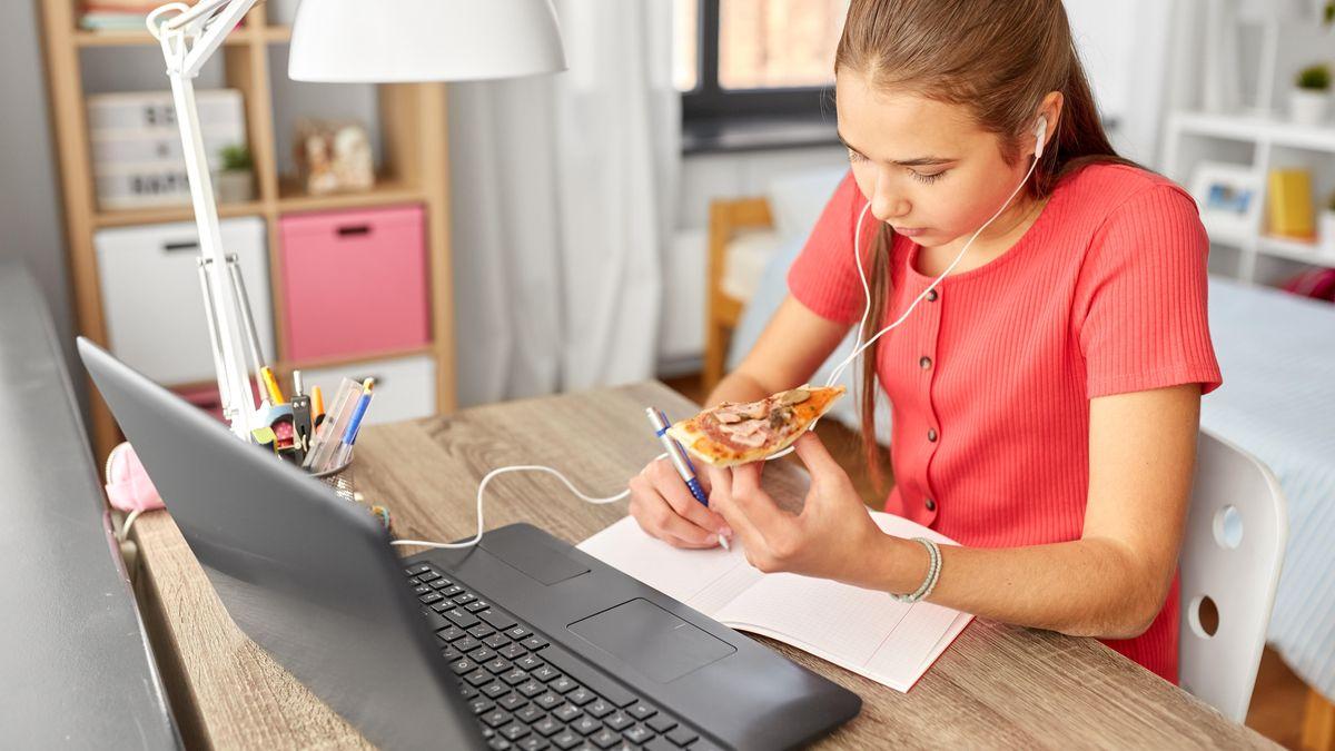Mädchen arbeitet mit einem Stück Pizza in der Hand vor einem Laptop