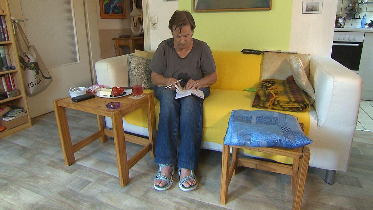 Christine Krögler auf ihrem Sofa, sie blättert in einem Notizbuch