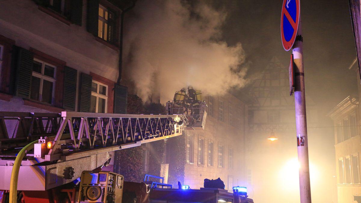 Qualm dringt aus einem Fenster, zwei Feuerwehrkräfte sind auf der Drehleiter direkt davor.