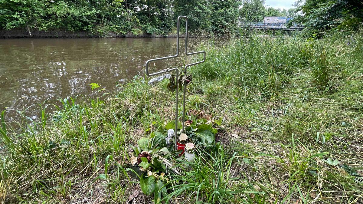 Kreuz mit Blumen und Kerzen am Weidener Flutkanal.