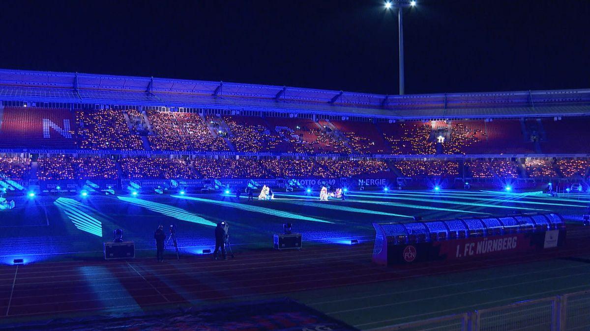 Im blau erleuchteten Nürnberger Max-Morlock-Stadion sitzen menschen mit Kerzen auf den Zuschauerrängen und singen Weihnachtslieder