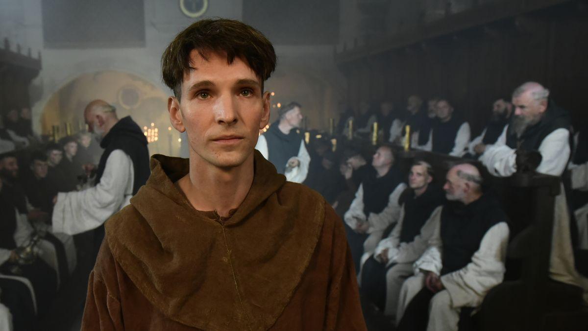 Ein junger Mönch steht frontal und schaut vermutlich auf einen Altar im Hintergund sitzen auf Bänken viele alte Mönche