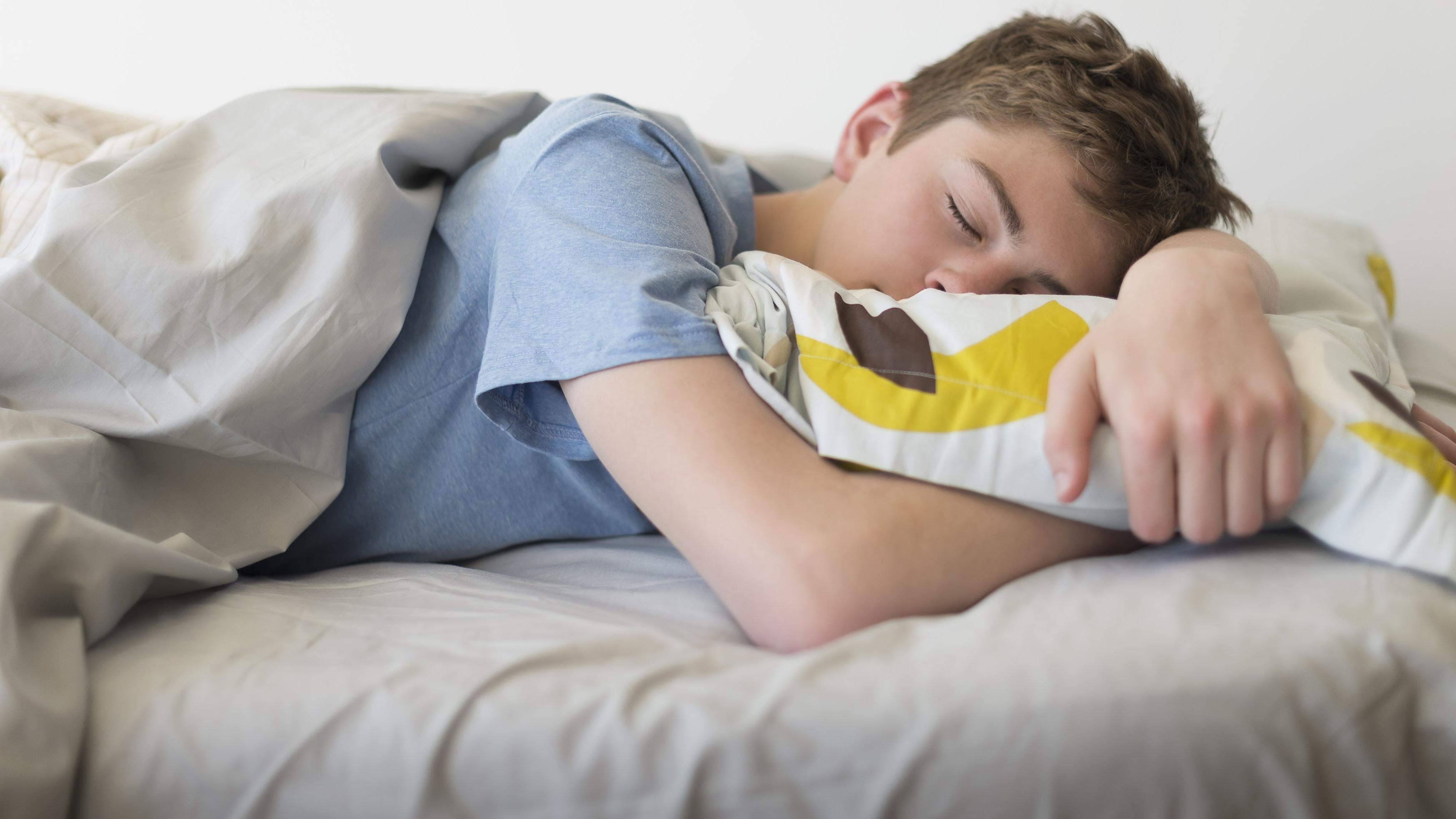 Schlafender Junge im Bett