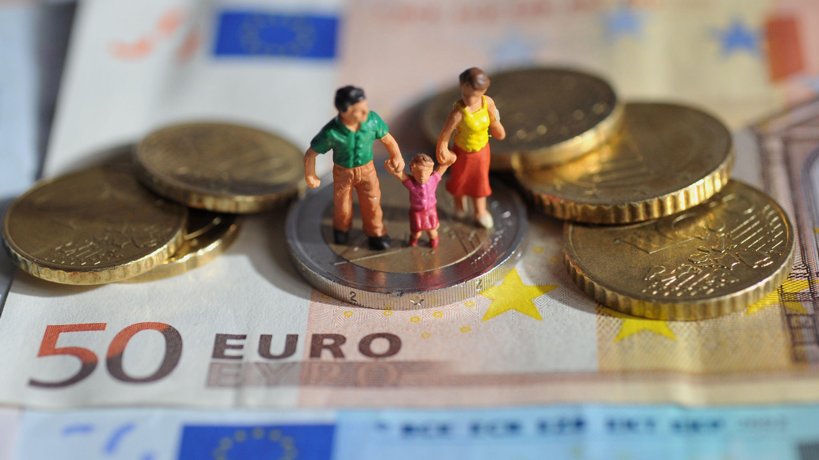 Eine Familie aus Spielzeugfiguren steht auf einem 50-Euro-Schein, darum ist Kleingeld angeordnet.