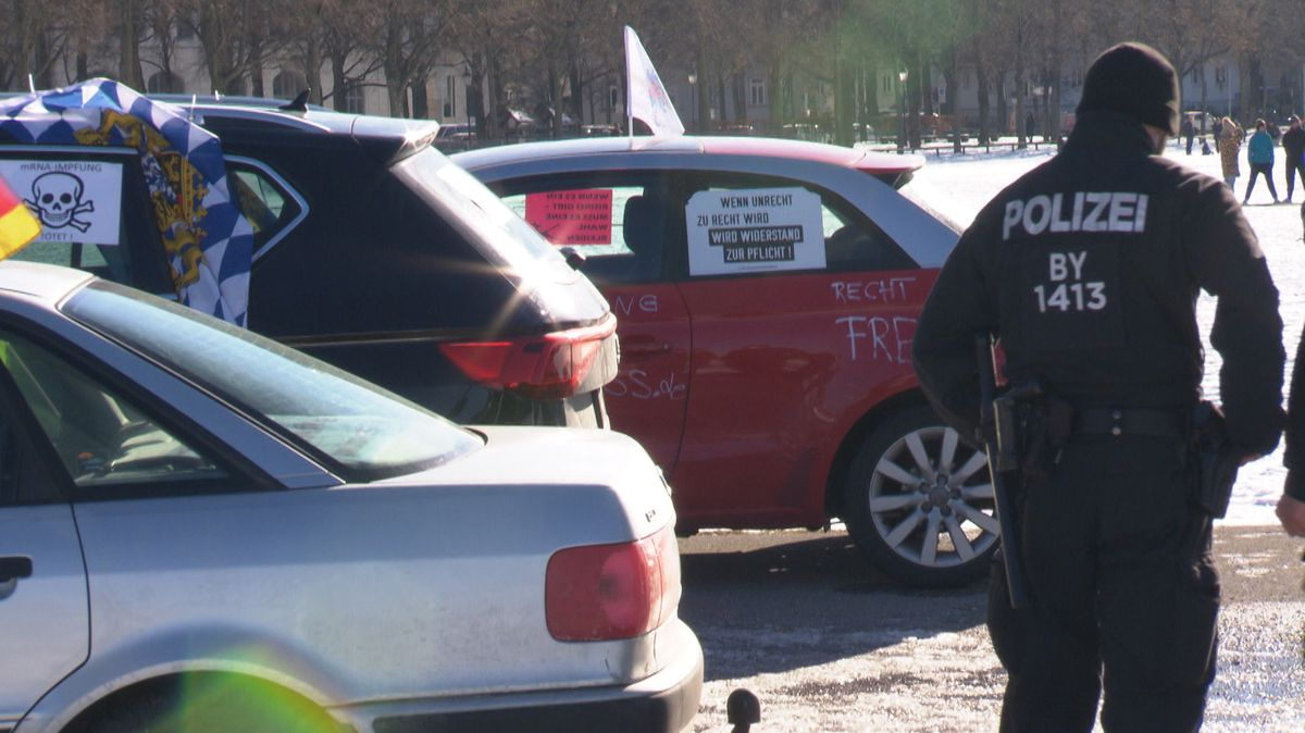 Polizisten und Teilnehmer des Autokorsos gegen die Corona-Maßnahmen.