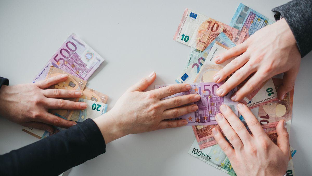 Die Hand einer Frau greift nach einem Geldschein, der auf einem Stapel weiterer Geldscheine unter Männerhänden liegt.