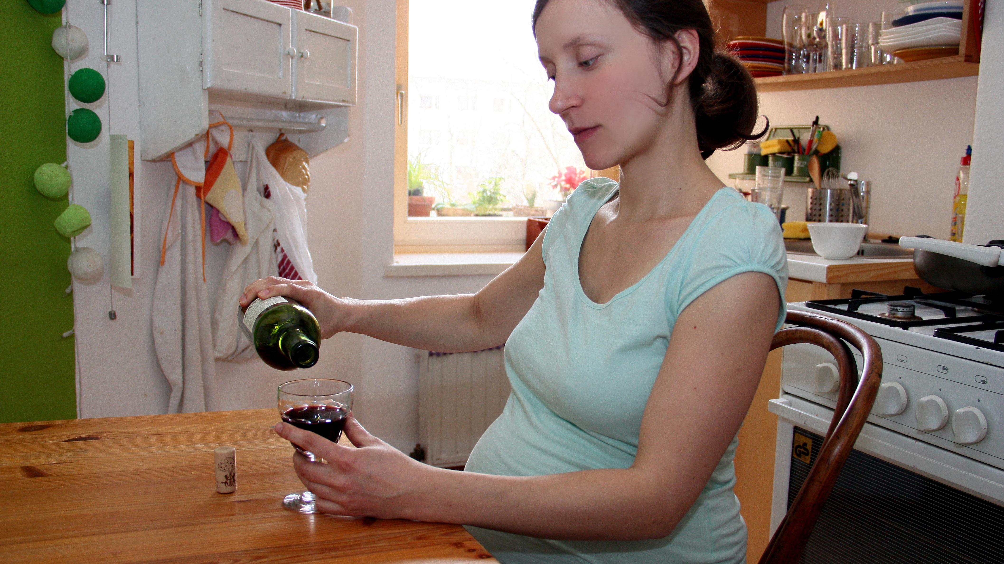Schwangere Frau schenkt sich ein Glas Rotwein ein (Symbolbild)