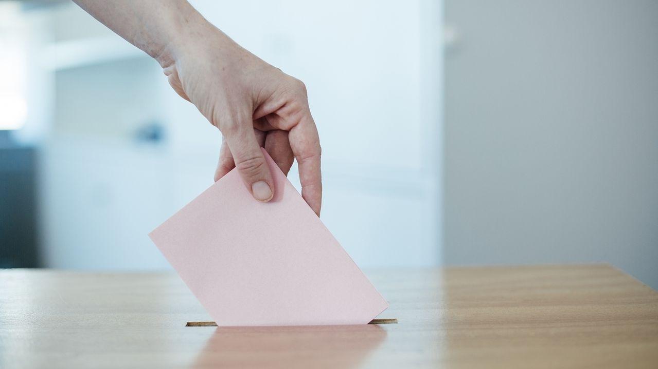 Jemand wirft einen Wahlzettel in eine Wahlurne (Symbolbild).