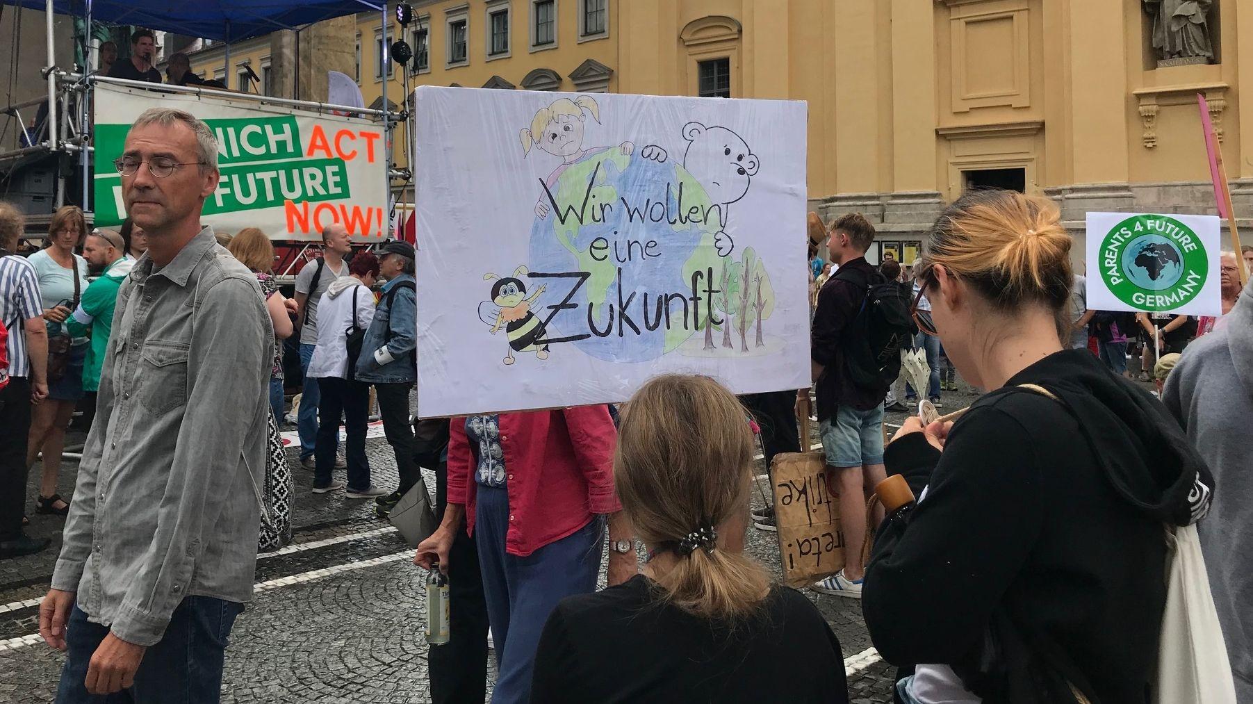 """Demonstration """"Munich for Future"""" Auf ein Plakat sind ein Kind, ein Eisbär und eine Biene gemalt, dazu ein Erdbal und die Aufschrift """"Wir wollen eure Zukunft."""""""