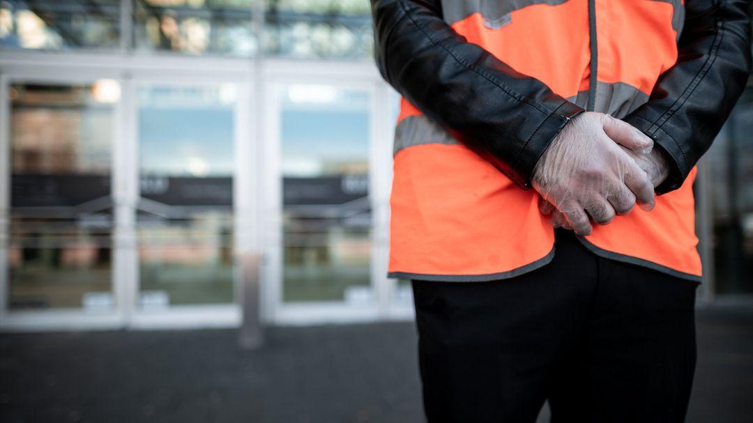 Ein Mitarbeiter eines Sicherheitsdienstes steht mit Handschuhen vor dem Eingang eines Einkaufszentrums.