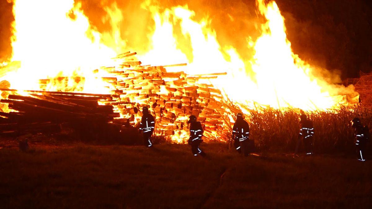 Einsatzkräfte der Feuerwehr stehen vor dem Feuer