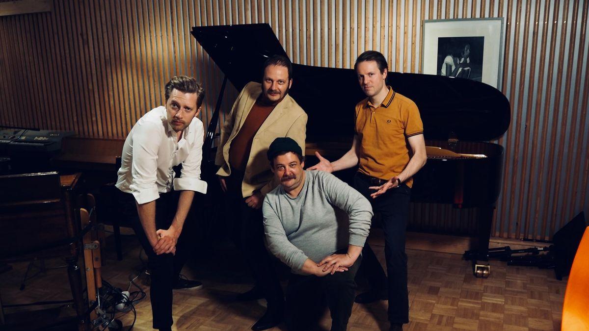 Drei Männer stehen in einem Aufnahmestudio um einen vierten Mann, der vor ihnen auf einem Stuhl sitzt.