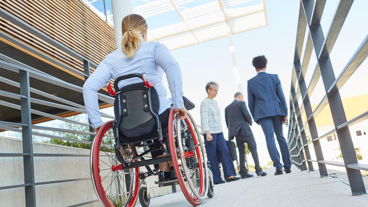 Mehrere Arbeitskollegen, darunter eine Rollstuhlfahrerin gehen über eine Rollstuhlrampe